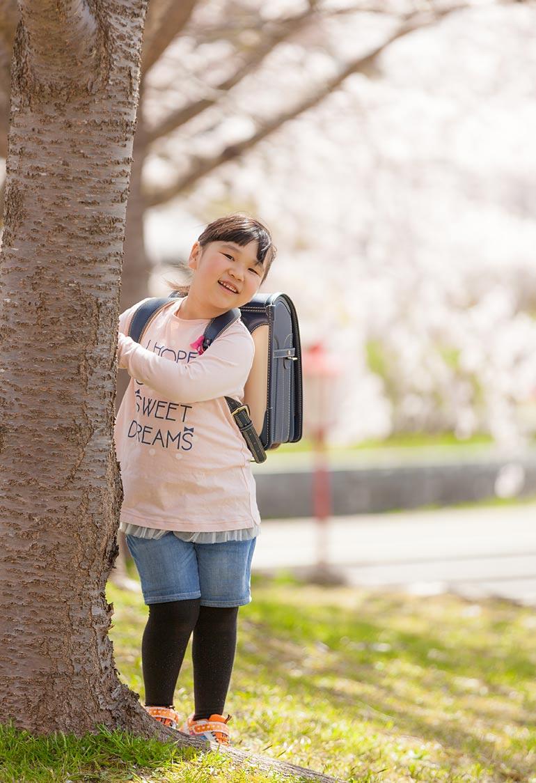 女の子-桜でランドセル背負う