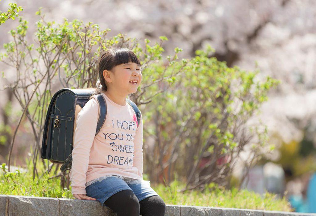 外の桜と入学する女の子